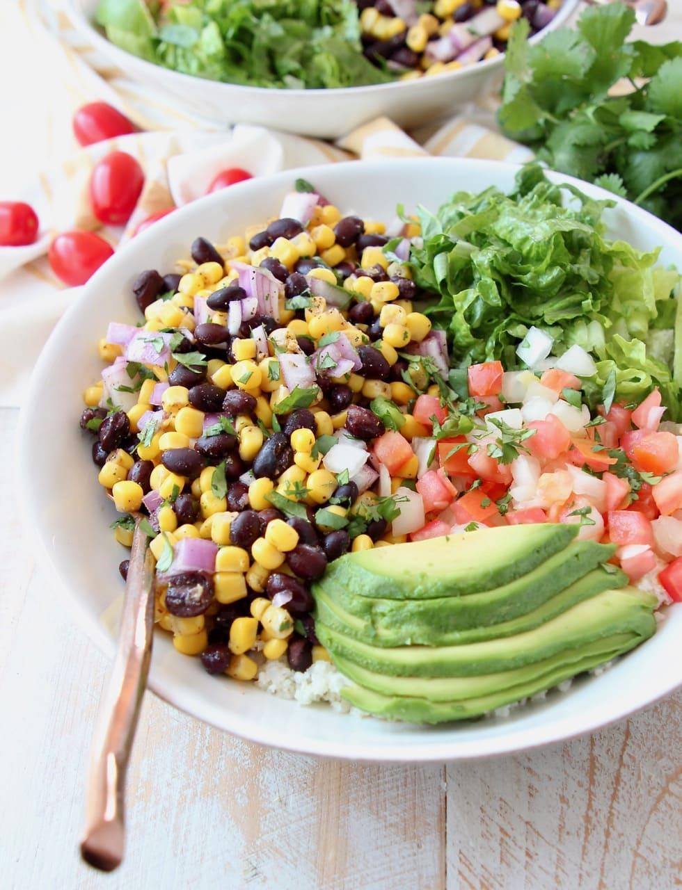 Vegan burrito bowl topped with avocado, black beans, corn, tomatoes and romaine lettuce