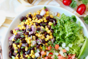 Overhead image of vegan burrito bowls filled with sliced avocado, corn, black beans and pico de gallo