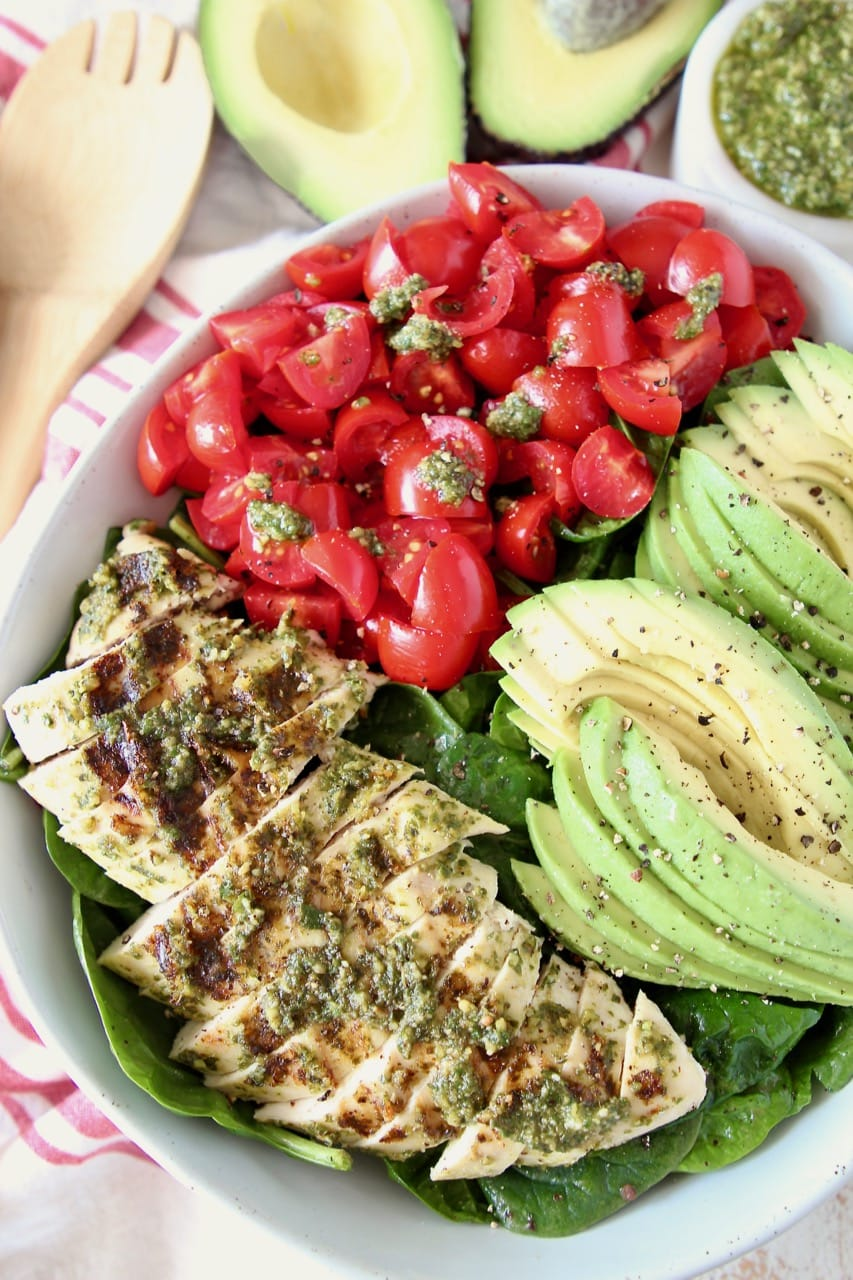 Sliced pesto chicken, sliced avocado and diced cherry tomatoes on top of spinach salad in bowl