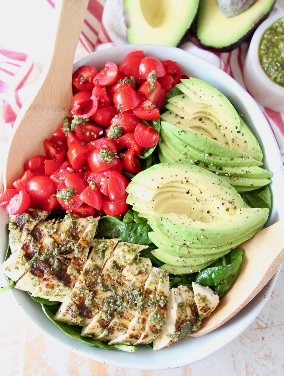 Sliced pesto chicken, sliced avocado, diced tomatoes and spinach in large bowl with wooden serving spoons