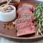 Sliced wagyu strip steak on wood tray with rosemary sprigs and black peppercorns
