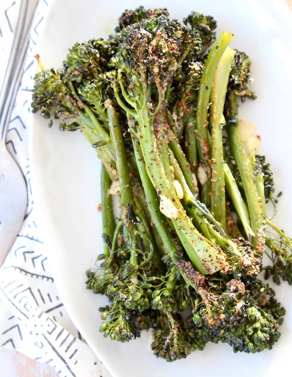 Garlic parmesan broccolini stacked up on top of each other on white plate