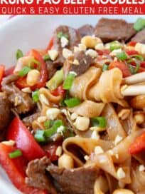 chopsticks swirling noodles in bowl with kung pao beef and peppers