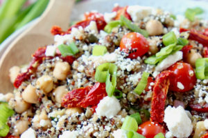 Quinoa salad in bowl with sun dried tomatoes and crumbled feta cheese