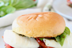 Grilled chicken on hamburger bun with fresh mozzarella cheese and tomatoes