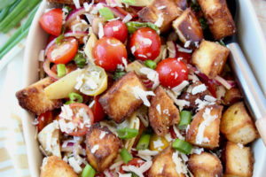 Overhead image of toasted bread salad in bowl with cherry tomatoes