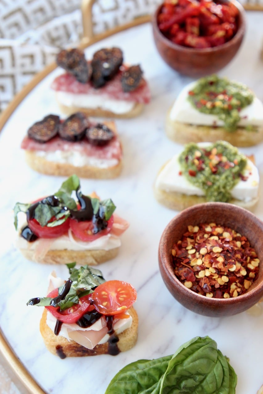 Crostini on marble serving tray with variety of toppings