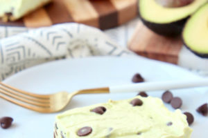 Avocado cheesecake bar with graham cracker crust on white plate with fork and chocolate chips