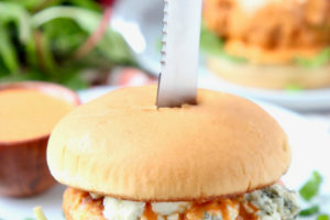 Buffalo chicken burger on bun with blue cheese crumbles, with knife stuck in the middle of the burger
