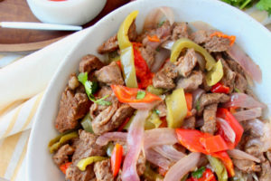 steak fajitas in white bowl with fresh cilantro on the side