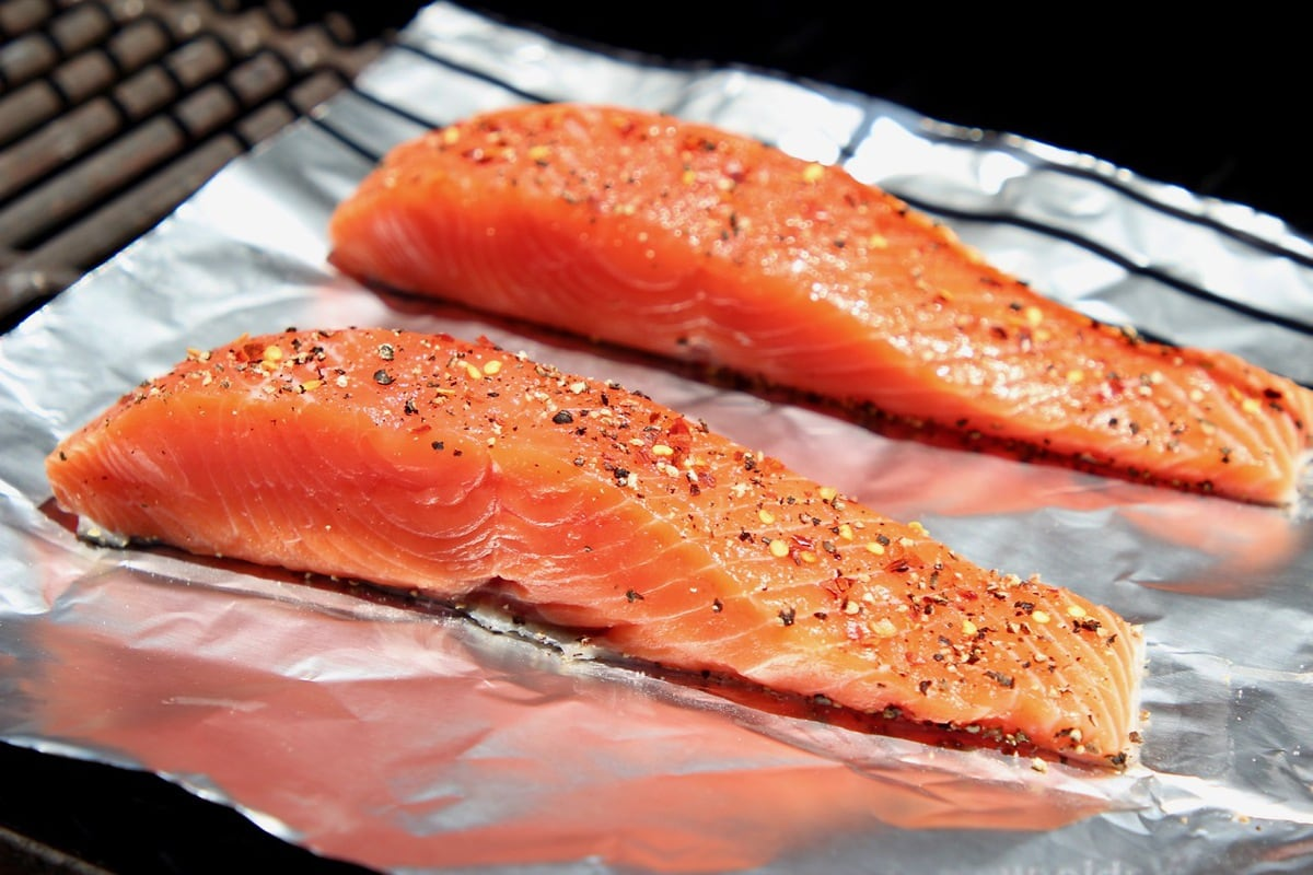 Two pieces of seasoned raw salmon on a piece of foil on the grill