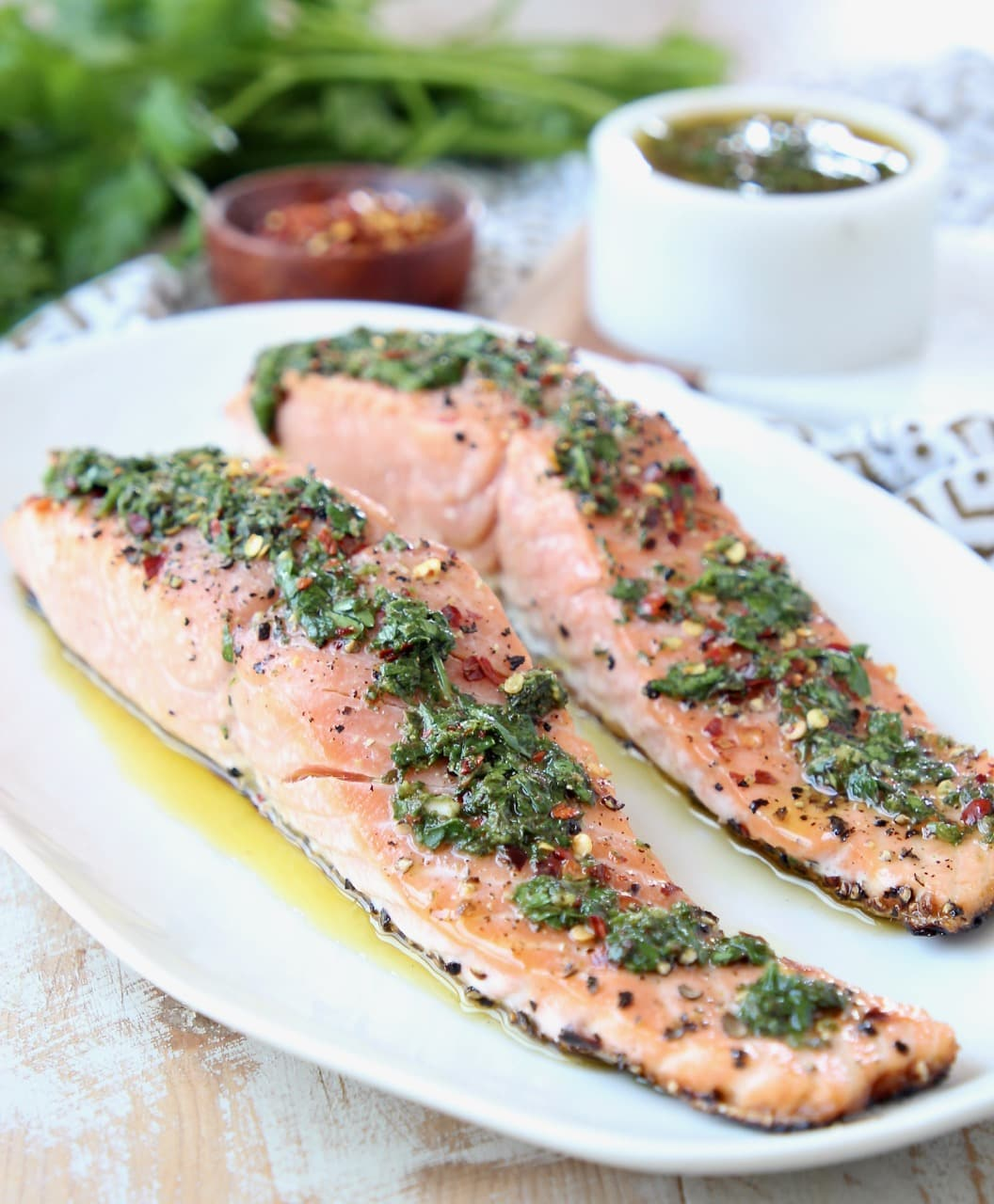 Two filets of grilled salmon on a white plate topped with chimichurri sauce