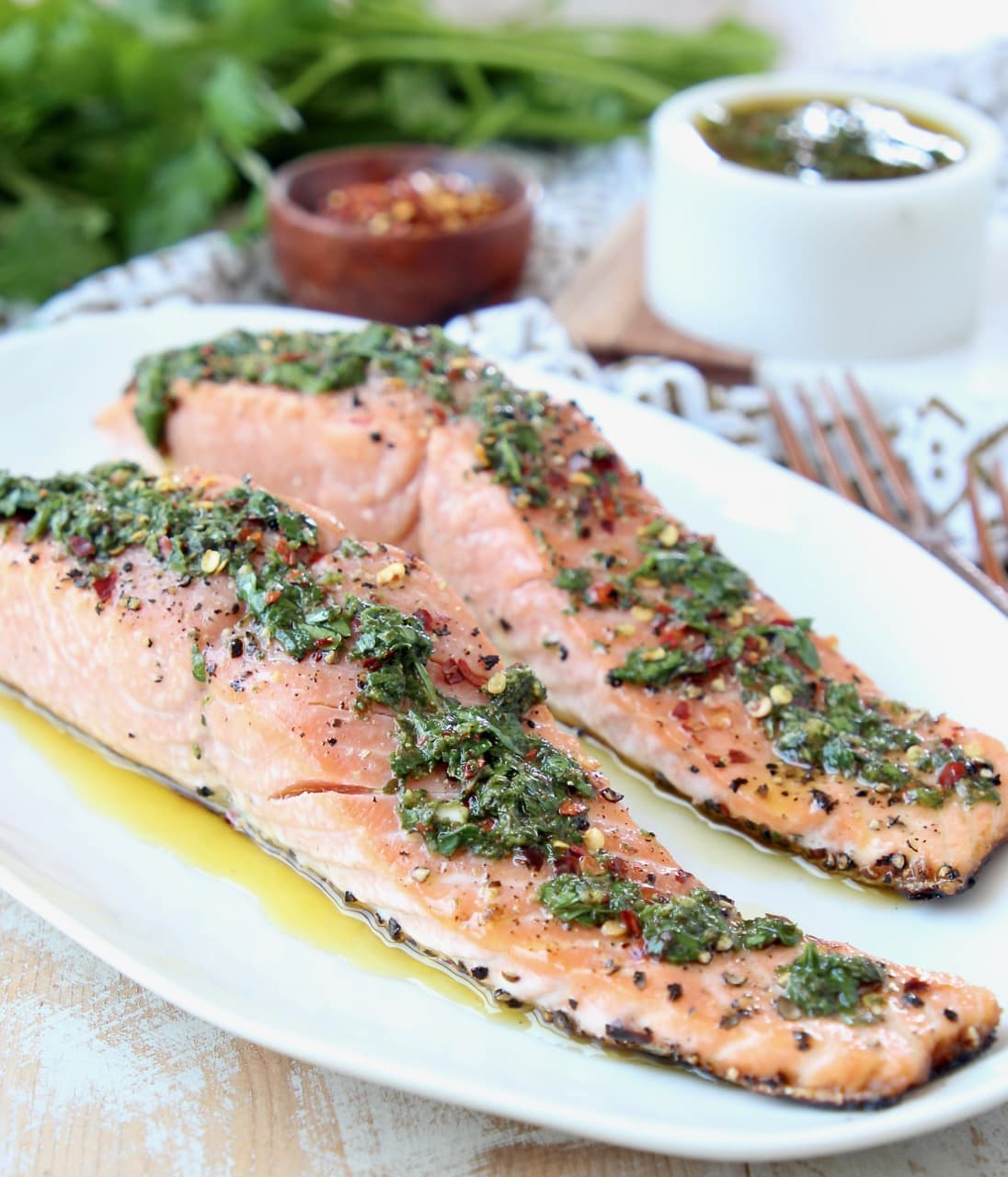 Slices of salmon on plate topped with chimichurri sauce