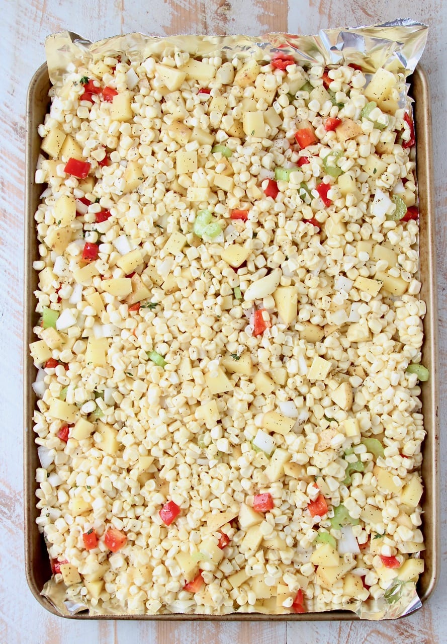 Corn, diced peppers and onions on foil lined baking sheet