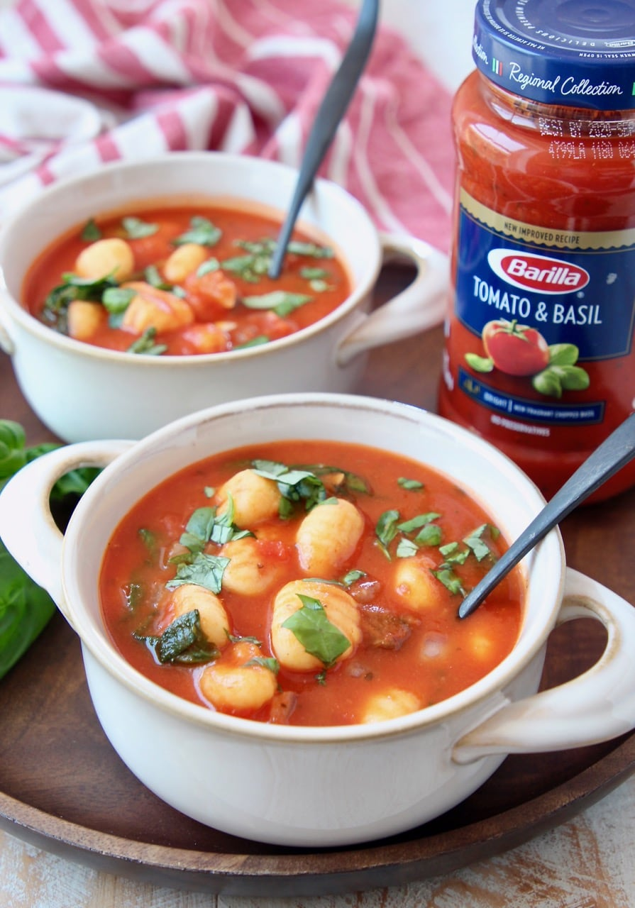 Gnocchi soup in white crocks with spoons