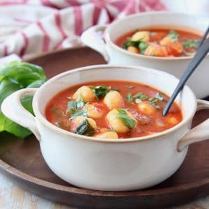 Tomato basil gnocchi soup in white bowls on wood tray