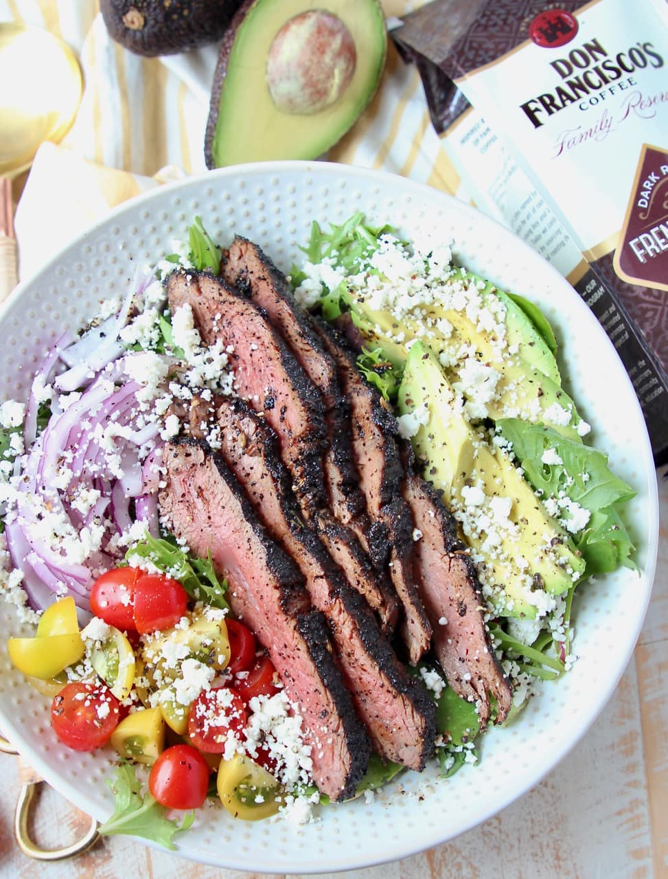 Steak salad in white bowl with bag of coffee and half an avocado on the side
