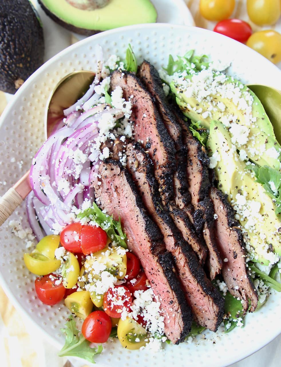 Grilled steak salad in a bowl with avocado, tomatoes and red onions