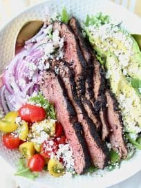 Grilled steak on top of salad in a white bowl with gold salad serving spoons