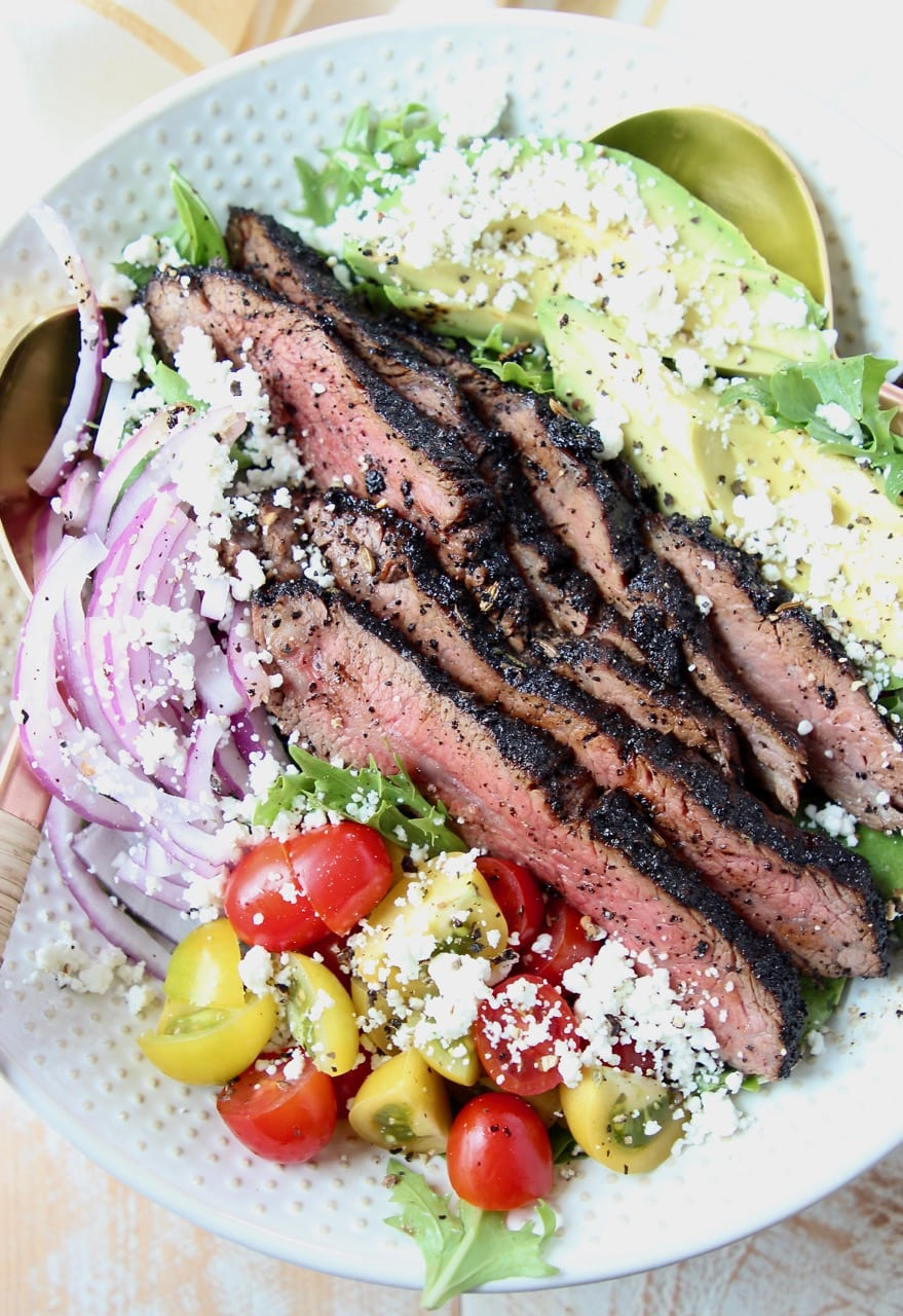 Steak salad in bowl with tomatoes, avocado and onions
