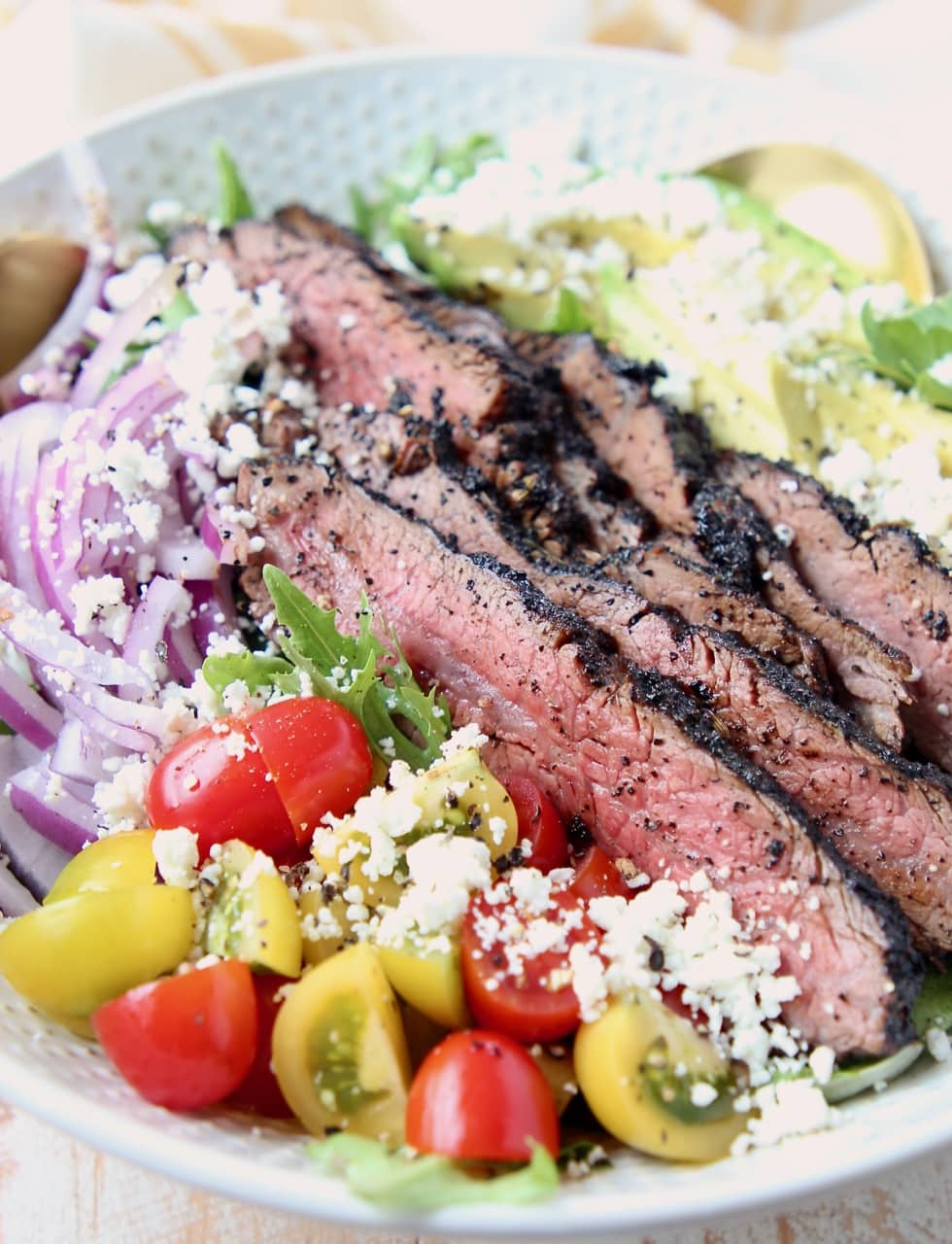 Sliced steak on a salad with cherry tomatoes, onions and goat cheese