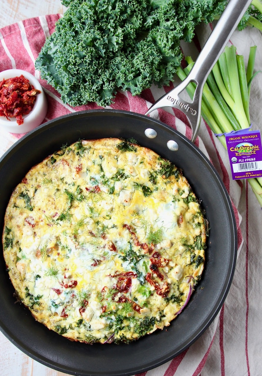 Vegetarian frittata in skillet with fresh kale and green onions on the side