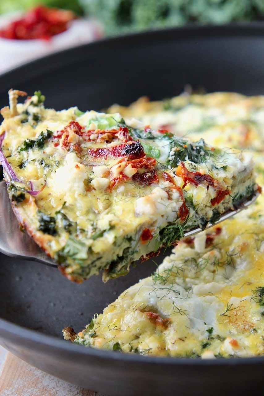 Slice of vegetable frittata lifted out of skillet with a spatula