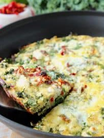 Slice of vegetable frittata being lifted out of skillet with silver spatula