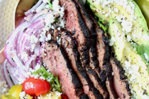 Coffee rubbed grilled steak salad in bowl with avocado, tomatoes and onions