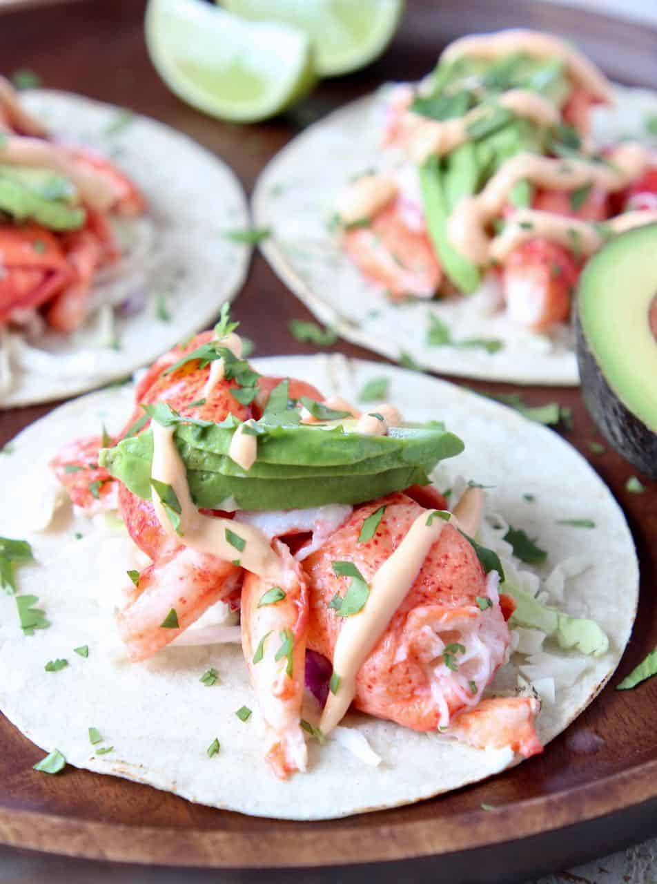 Lobster tacos topped with avocado on wood serving tray