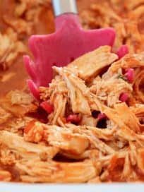 Shredded buffalo chicken with red serving spoon