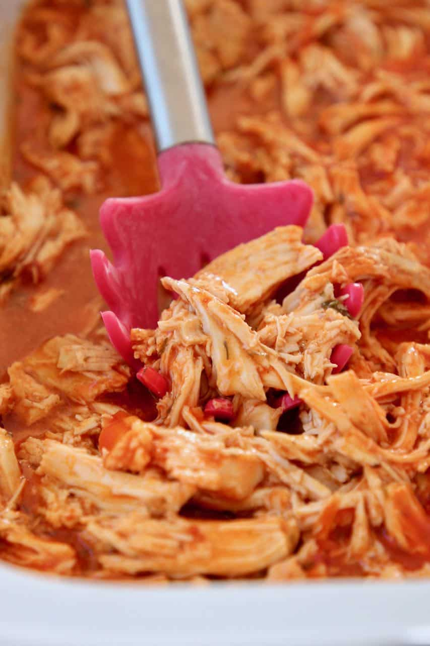 Shredded buffalo chicken in crock pot with red spoon