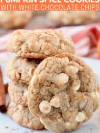 Stacked up white chocolate chip cookies on plate with one cookie on its side