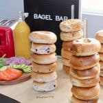 Bagel bar setup with bagels on stands and bagel bar sign in background
