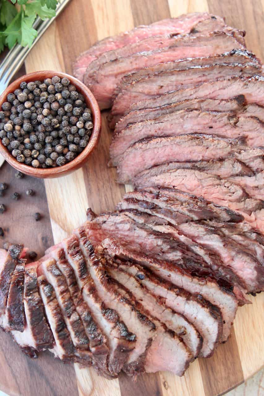 Sliced tri tip steak on wood cutting board with a bowl of black peppercorns