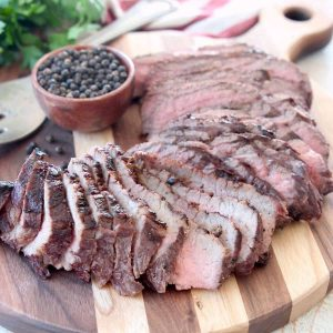 Sliced grilled tri tip on wood cutting board