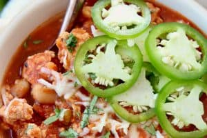 Buffalo chicken chili in bowl, topped with fresh jalapenos