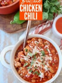 Overhead image of buffalo chicken chili in bowl topped with shredded cheese