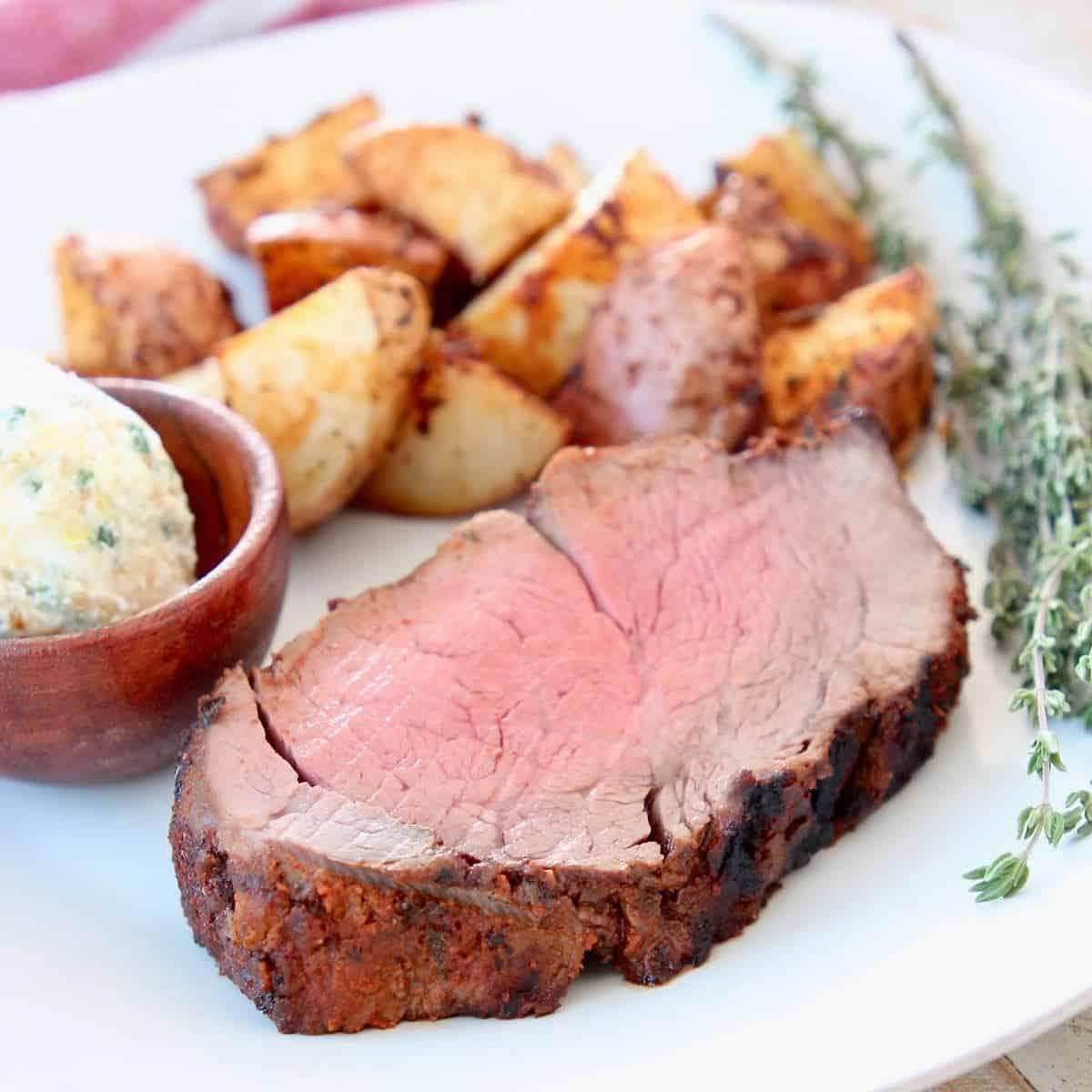 Slice of blackened beef tenderloin on plate with potatoes and herb butter in wood ramekin