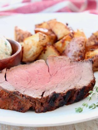 Slice of beef tenderloin on plate with fresh herbs and potatoes