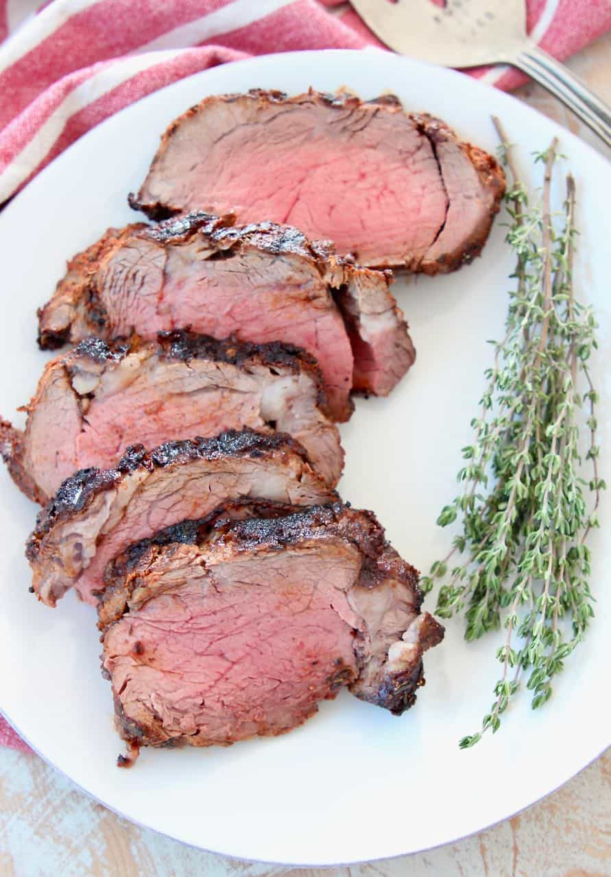 Slices of blackened beef tenderloin on white plate with fresh herbs