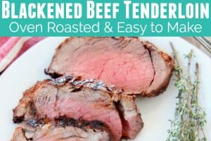 Sliced blackened beef tenderloin on plate with herbs