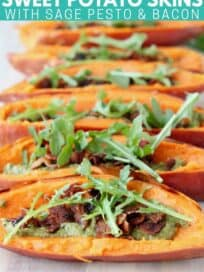 sweet potato skins filled with pesto, crumbled bacon and arugula on wood cutting board