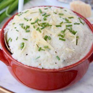 Cheesy mashed cauliflower in dark orange bowl