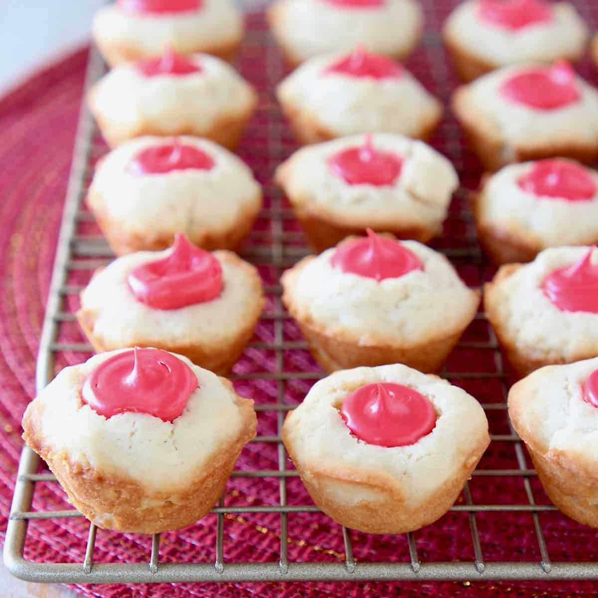 Sugar cookie cups with red frosting filling sitting on wire rack
