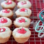 Sugar cookie cups with red frosting filling sitting on wire cooling rack