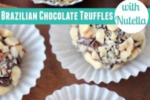 Chocolate truffles rolled in chopped nuts in white paper candy cups