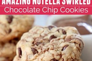 Stacked up nutella chocolate chip cookies with hand holding one cookie cut in half
