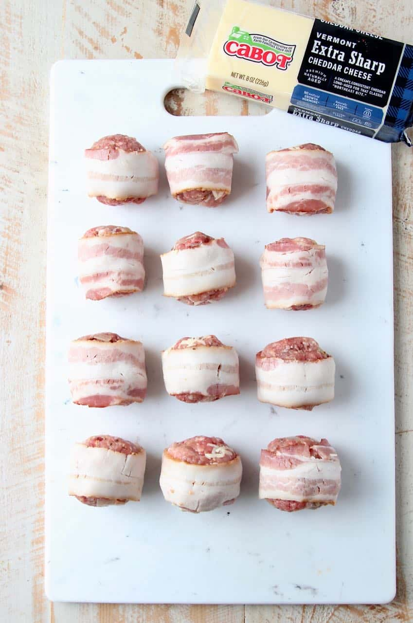 Raw bacon wrapped meatballs on white cutting board