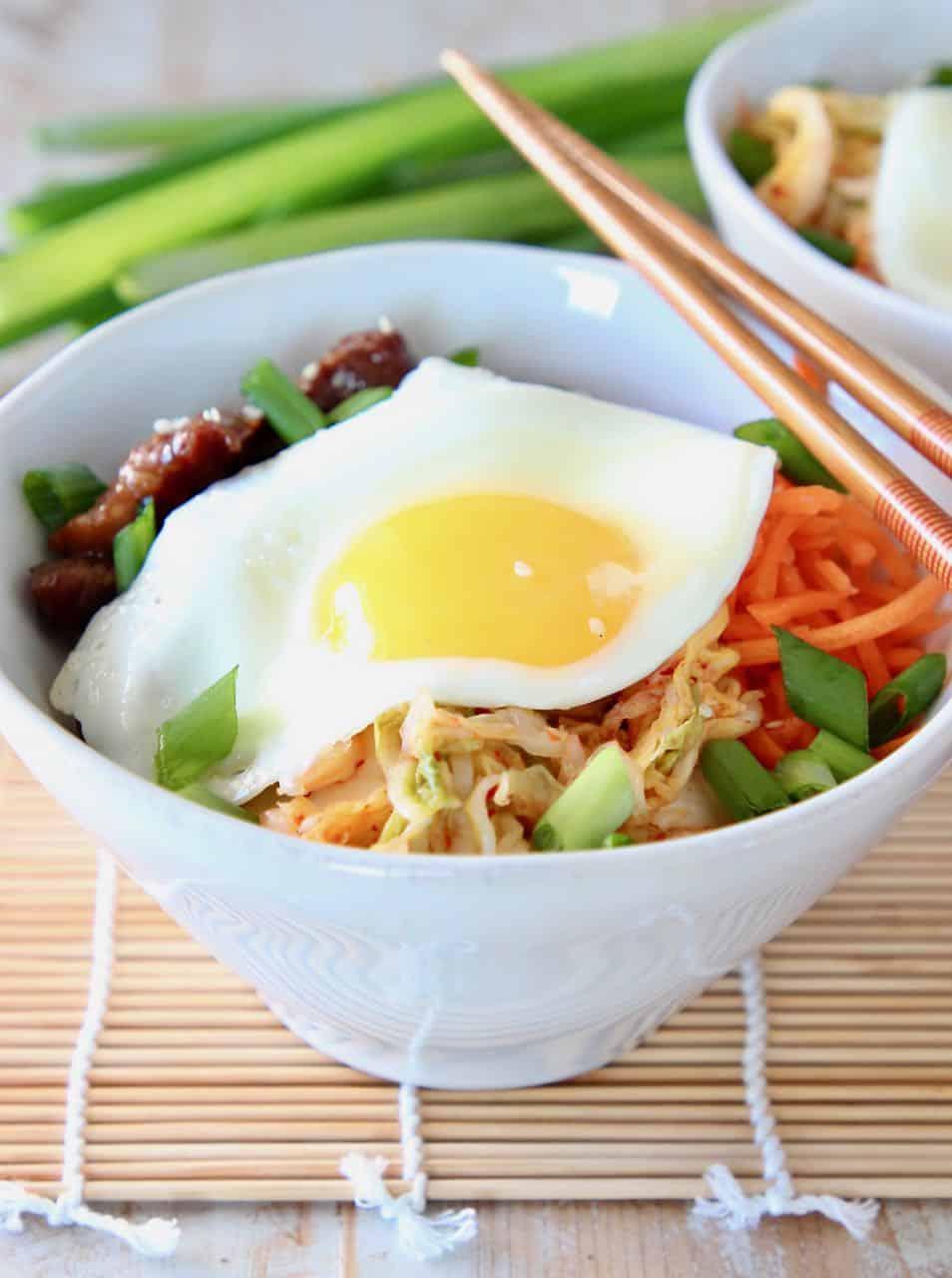 Korean BBQ Cauliflower Rice Bowl topped with a fried egg and chopsticks